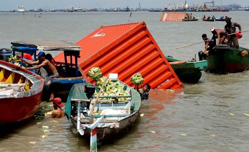 Sejumlah nelayan mengambil barang-barang berupa mie instan yang ada di salah satu kontainer muatan Kapal Kargo Journey yang tenggelam usai bertabrakan dengan KM Lambelu, di Buoy 10 Selat Madura, Tanjung Perak Surabaya, Selasa (1/4)